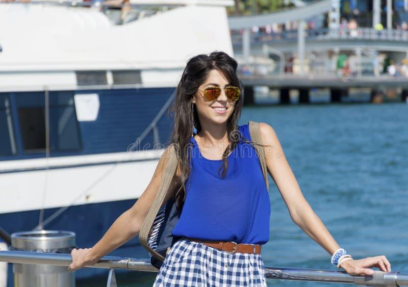 Νέα χαμογελώντας γυναίκα με τα χρυσά γυαλιά ηλίου που κάθεται σε μια αποβάθρα θάλασσας στη Βαρκελώνη στοκ φωτογραφία
