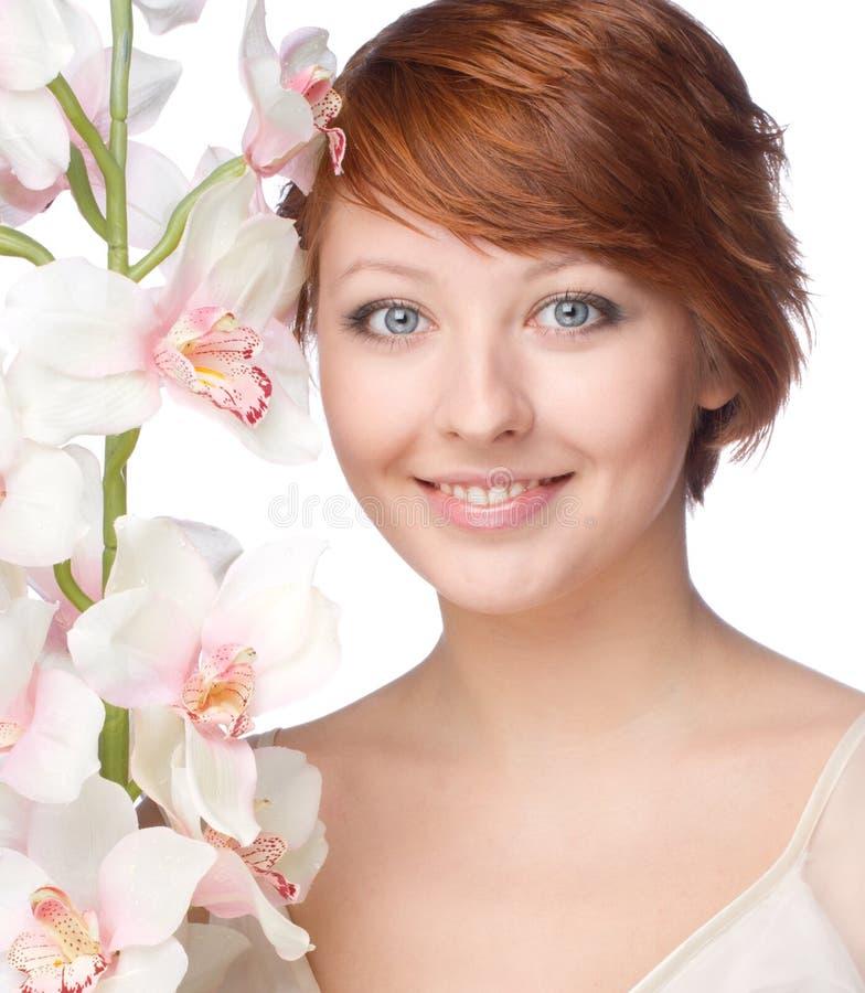 Νέα χαμογελώντας γυναίκα με τη ορχιδέα στοκ φωτογραφία με δικαίωμα ελεύθερης χρήσης