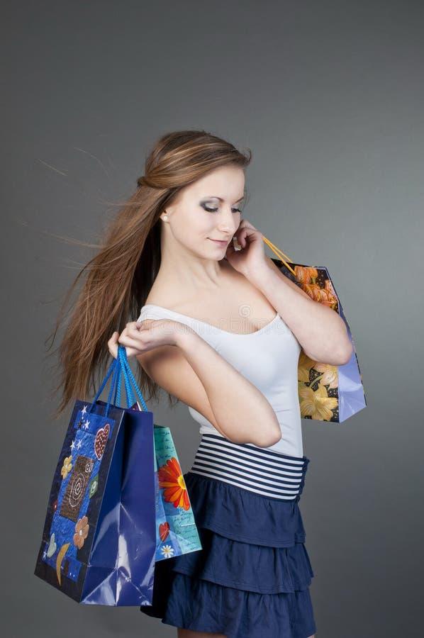 Νέα χαμογελώντας γυναίκα με τις τσάντες αγορών πέρα από το γκρίζο υπόβαθρο στοκ εικόνες