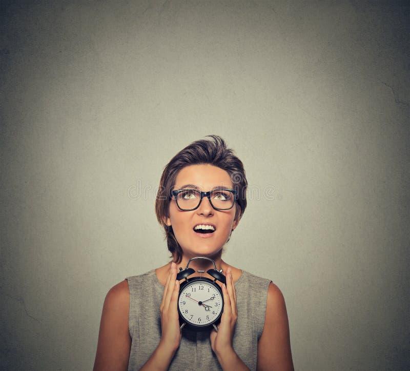 Νέα χαμογελώντας γυναίκα με το ξυπνητήρι που ανατρέχει στοκ φωτογραφία με δικαίωμα ελεύθερης χρήσης