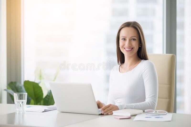 Νέα χαμογελώντας γυναίκα που εργάζεται με το lap-top στοκ φωτογραφία με δικαίωμα ελεύθερης χρήσης