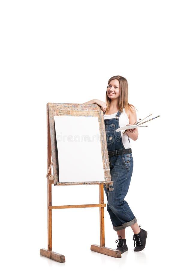 Νέα χαμογελώντας γυναίκα που στέκεται easel στοκ φωτογραφίες με δικαίωμα ελεύθερης χρήσης