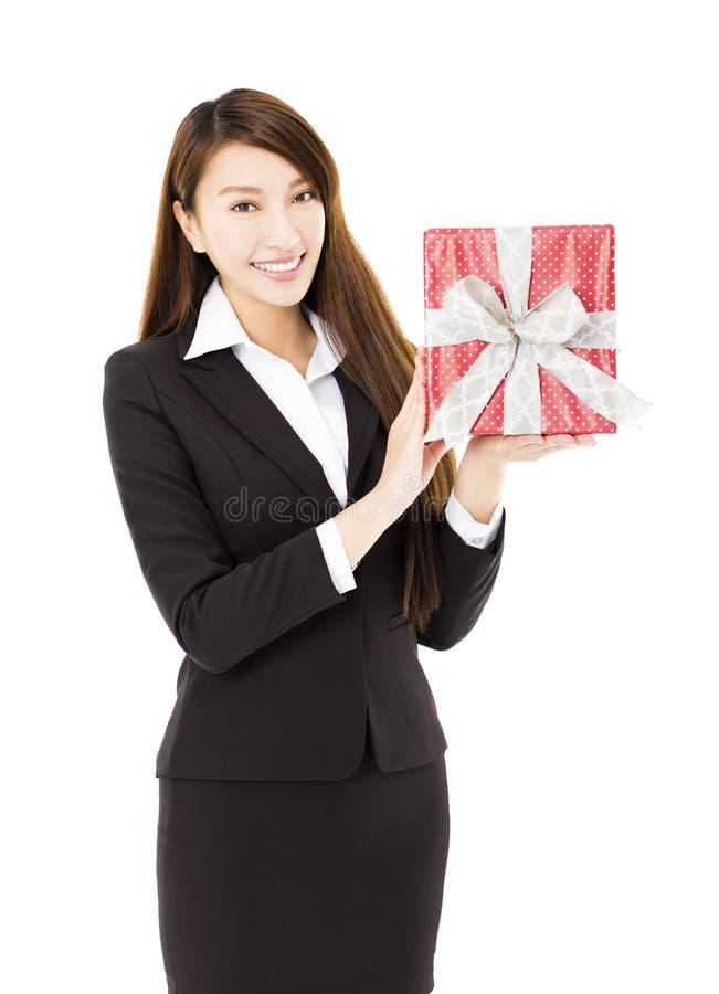 Νέα χαμογελώντας επιχειρηματίας που παρουσιάζει κιβώτιο δώρων στοκ εικόνες