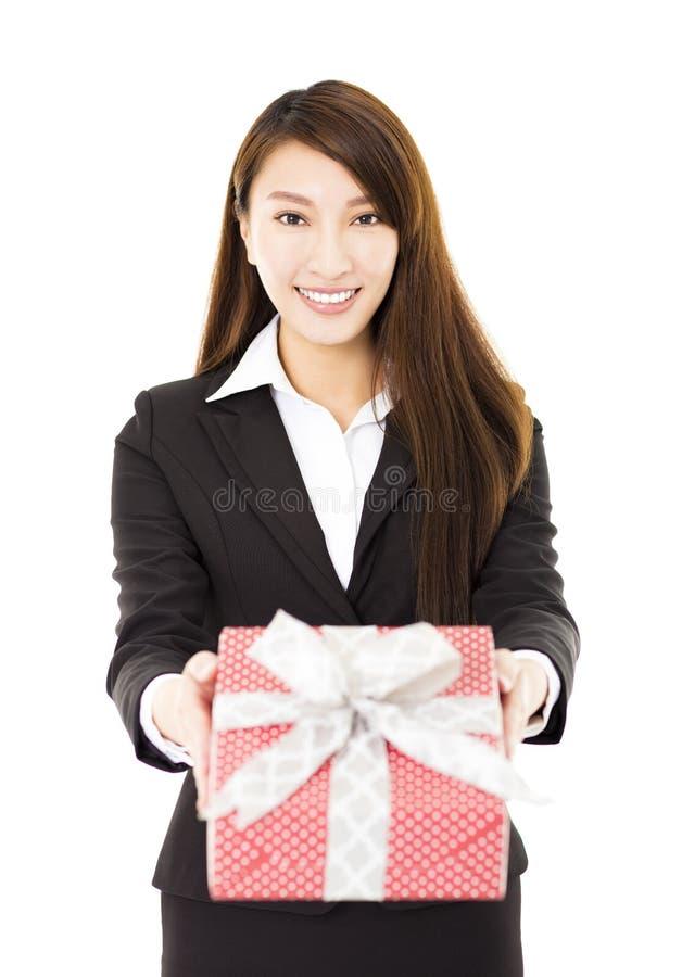 Νέα χαμογελώντας επιχειρηματίας που παρουσιάζει κιβώτιο δώρων στοκ φωτογραφίες
