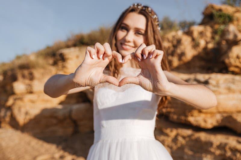 Νέα χαμογελώντας νύφη που παρουσιάζει χειρονομία καρδιών με τα χέρια στοκ εικόνες με δικαίωμα ελεύθερης χρήσης