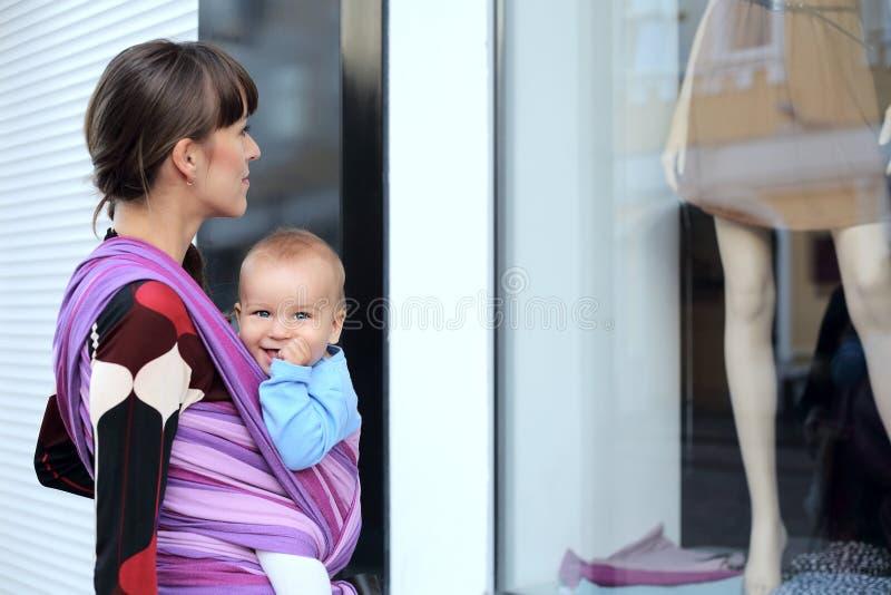 Νέα χαριτωμένη μητέρα με το μωρό στη σφεντόνα στοκ φωτογραφία