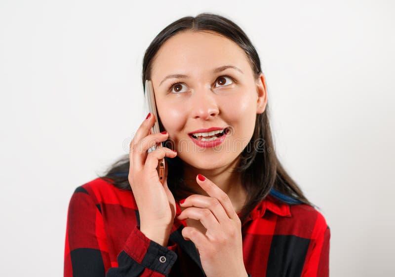 Νέα χαριτωμένη όμορφη γυναίκα κοριτσιών στο κόκκινο πουκάμισο καρό στο άσπρο υπόβαθρο που μιλά στο smartphone και το χαμόγελο στοκ εικόνα με δικαίωμα ελεύθερης χρήσης