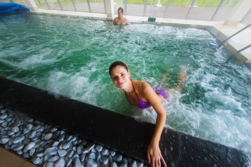 Νέα χαλάρωση γυναικών σε μια εσωτερική λίμνη στοκ εικόνες