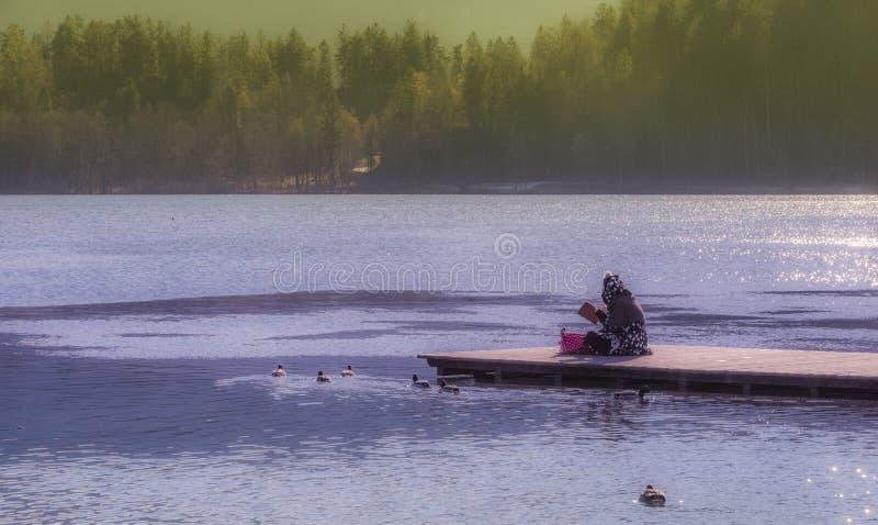 Νέα χαλάρωση γυναικών στην αιμορραγημένη αποβάθρα λιμνών στοκ εικόνα