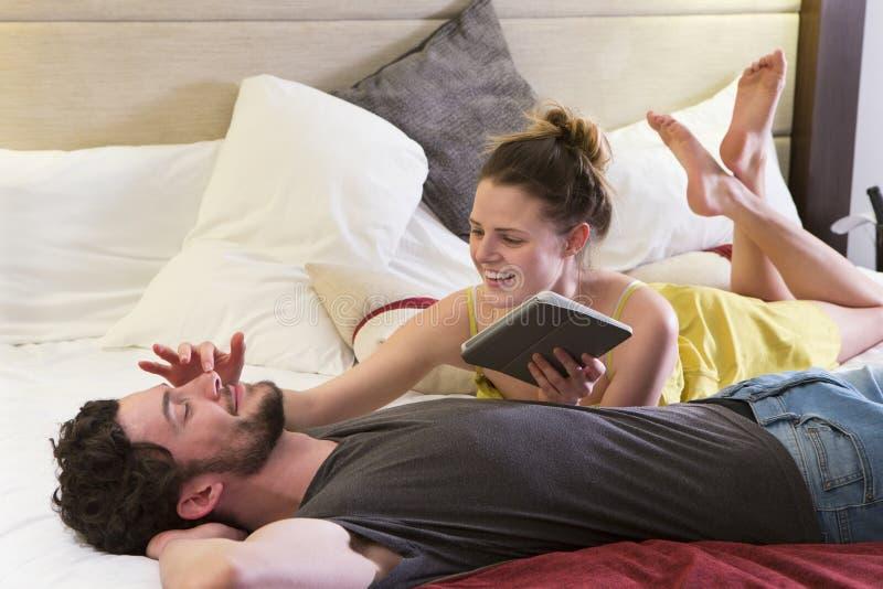 Νέα χαλάρωση ζευγών στο δωμάτιο ξενοδοχείου τους στοκ εικόνα με δικαίωμα ελεύθερης χρήσης