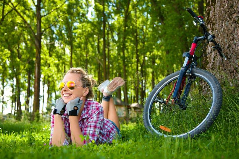 Νέα χαλάρωση ποδηλατών που βρίσκεται στη χλόη στοκ εικόνες με δικαίωμα ελεύθερης χρήσης