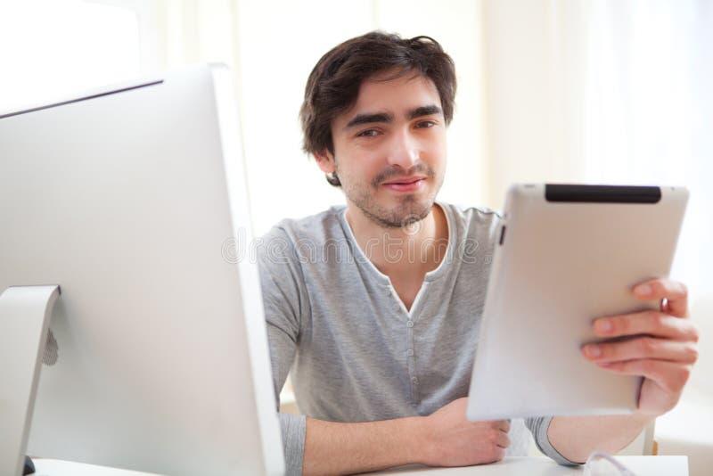 νέα χαλαρωμένα άτομα στο γραφείο που χρησιμοποιεί την ταμπλέτα στοκ εικόνες