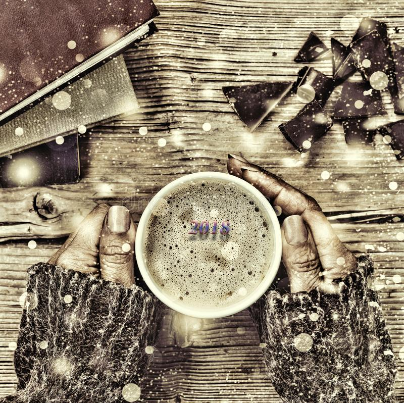 Νέα Χριστούγεννα έτους Ένα φλιτζάνι του καφέ ή ένα φλυτζάνι του τσαγιού στο χέρι του, και οι γυναίκες συνέτριψαν τη σκοτεινή σοκο στοκ εικόνα