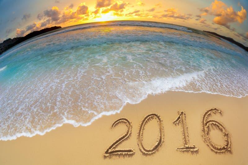 2016 νέα ψηφία έτους που γράφονται στην άμμο παραλιών στοκ εικόνα