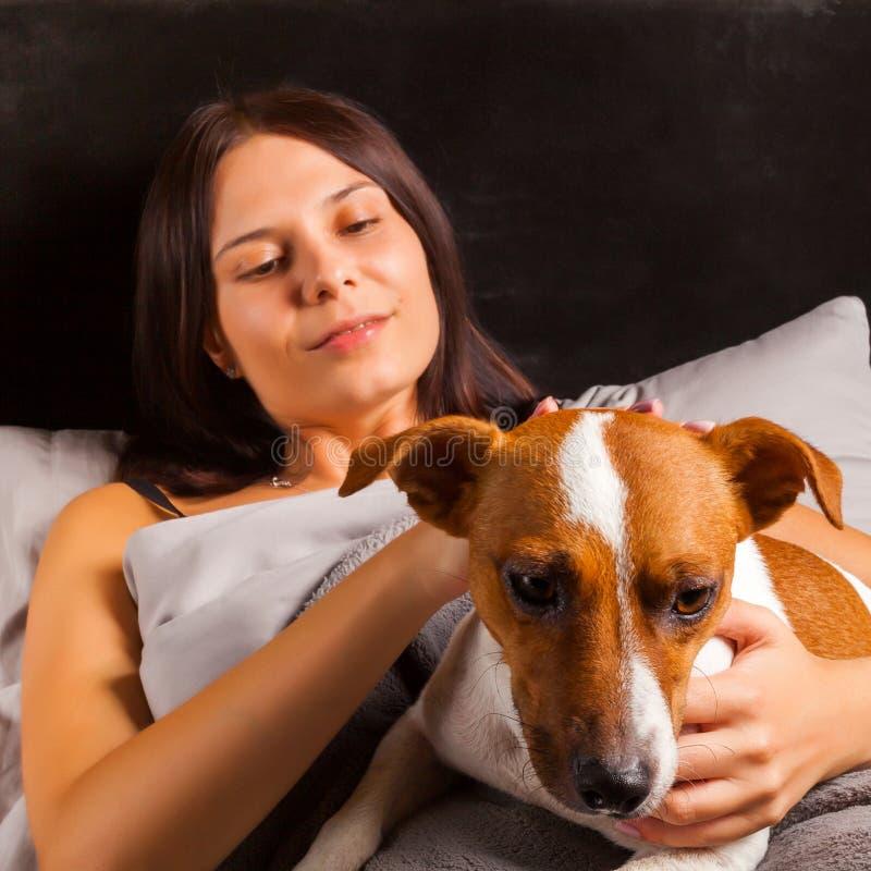 Νέα όμορφα παιχνίδια γυναικών brunette στο κρεβάτι με το σκυλί της στοκ φωτογραφίες
