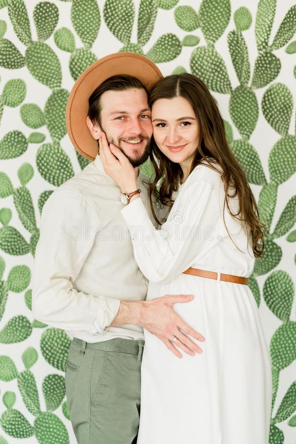 Νέα όμορφη έγκυος γυναίκα και ο σύζυγός της στο καπέλο που στέκεται κοντά στον τοίχο κάκτων στοκ εικόνα με δικαίωμα ελεύθερης χρήσης