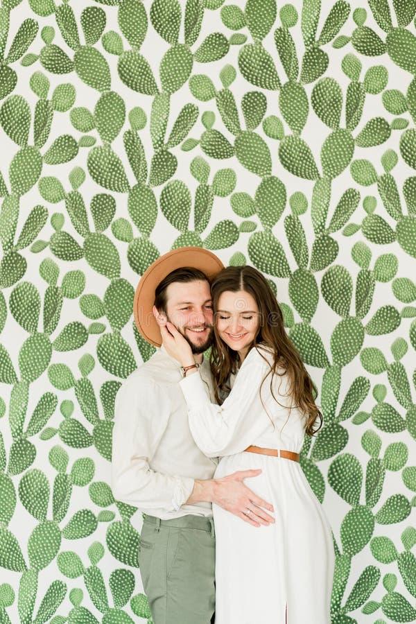 Νέα όμορφη έγκυος γυναίκα και ο σύζυγός της στο καπέλο που στέκεται κοντά στον τοίχο κάκτων στοκ φωτογραφία με δικαίωμα ελεύθερης χρήσης