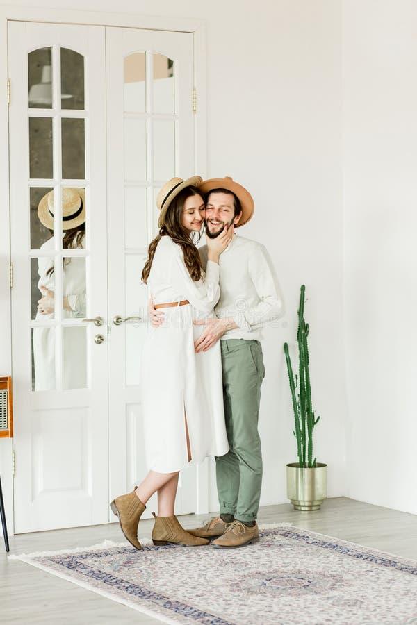 Νέα όμορφη έγκυος γυναίκα και ο σύζυγός της στο καπέλο που στέκεται κοντά στον τοίχο κάκτων στοκ φωτογραφίες με δικαίωμα ελεύθερης χρήσης