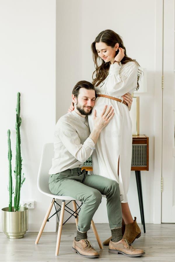 Νέα όμορφη έγκυος γυναίκα και ο σύζυγός της στο καπέλο που στέκεται κοντά στον τοίχο κάκτων στοκ εικόνες