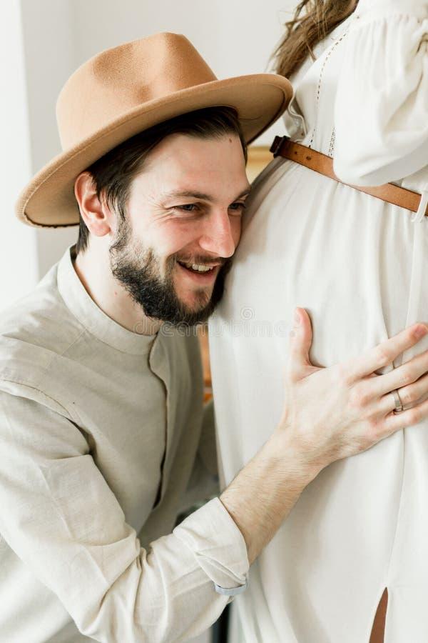Νέα όμορφη έγκυος γυναίκα και ο σύζυγός της στο καπέλο που στέκεται κοντά στον τοίχο κάκτων στοκ φωτογραφία