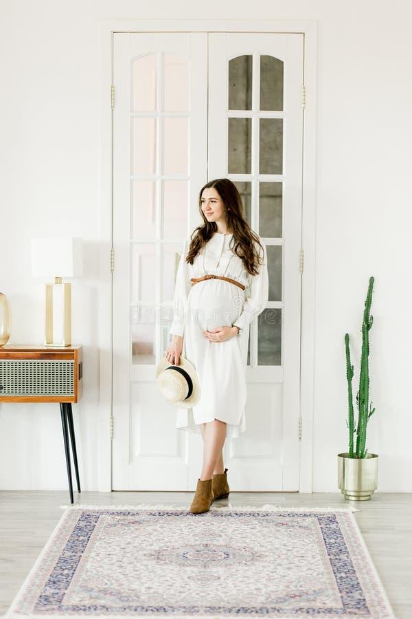 Νέα όμορφη έγκυος γυναίκα στο καπέλο που στέκεται κοντά στις άσπρες πόρτες στοκ εικόνα