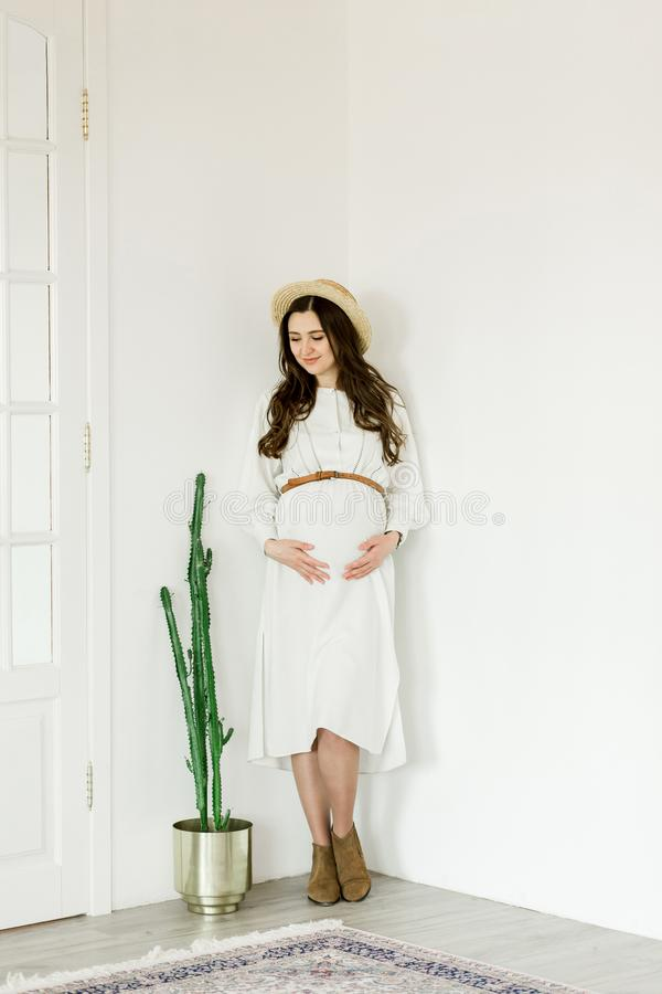 Νέα όμορφη έγκυος γυναίκα στο καπέλο που στέκεται κοντά στον άσπρο τοίχο στοκ εικόνα