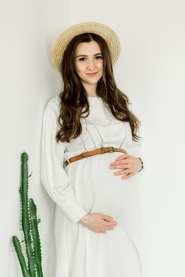 Νέα όμορφη έγκυος γυναίκα στο καπέλο που στέκεται κοντά στον τοίχο κάκτων στοκ φωτογραφία με δικαίωμα ελεύθερης χρήσης