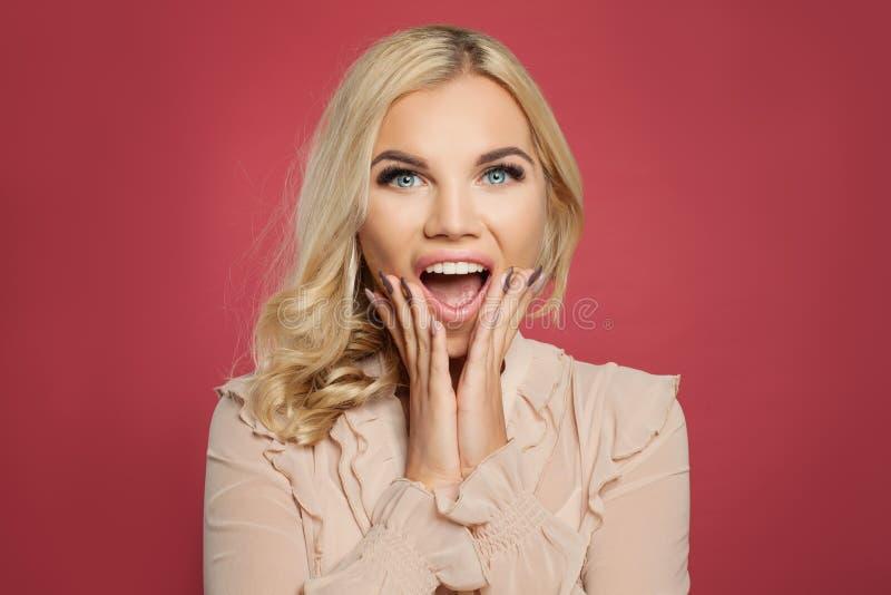 Νέα όμορφη έκπληκτη γυναίκα με το ανοιγμένο στόμα Πορτρέτο του αρκετά σγουρού κοριτσιού τρίχας στο φωτεινό ρόδινο υπόβαθρο στοκ εικόνες