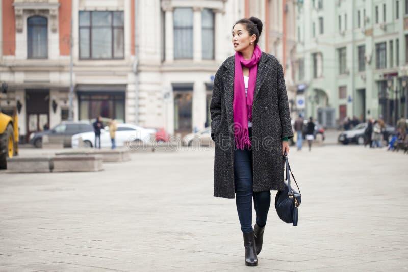 Νέα όμορφη ασιατική γυναίκα στο μοντέρνο γκρίζο παλτό στοκ εικόνες