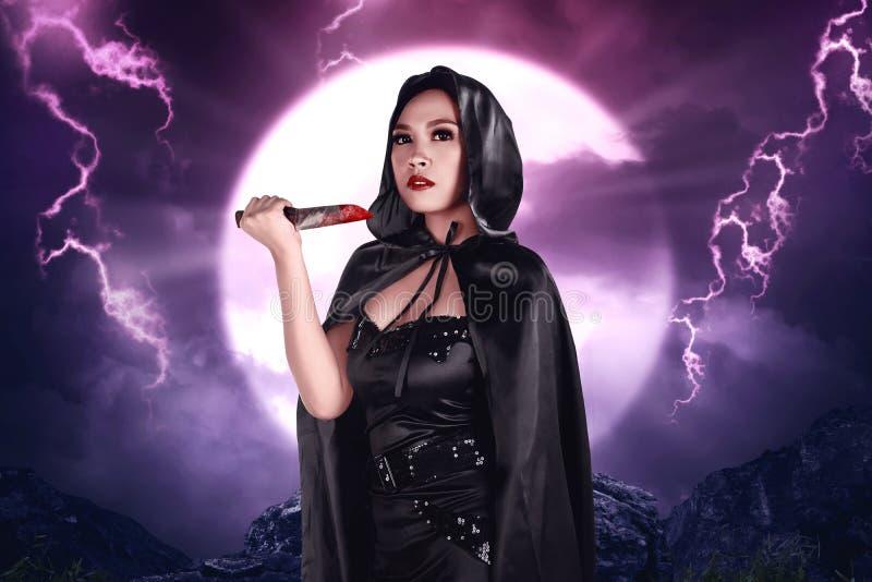 Νέα όμορφη ασιατική μάγισσα που κρατά το αιματηρό μαχαίρι στοκ εικόνα με δικαίωμα ελεύθερης χρήσης