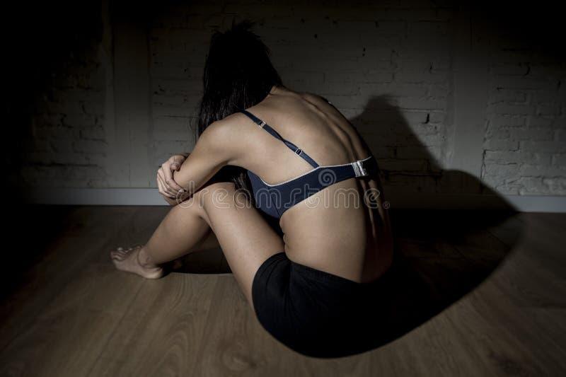 Νέα όμορφη λατινική συνεδρίαση κοριτσιών γυναικών ή εφήβων λυπημένη και μόνη στο νεβρικό αίσθημα σκοταδιού που πιέζεται στοκ εικόνα