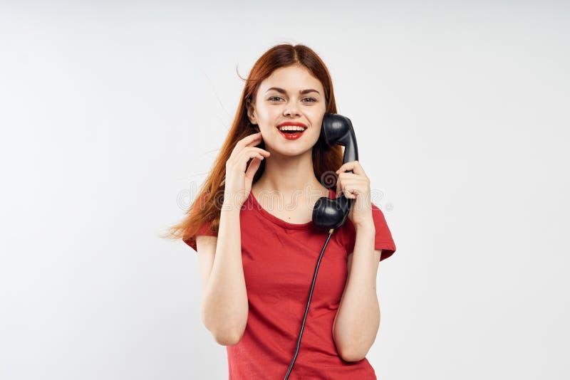Νέα όμορφη γυναίκα απομονωμένη στη λευκό κλήση υποβάθρου στο τηλέφωνο γραμμών εδάφους στοκ φωτογραφία