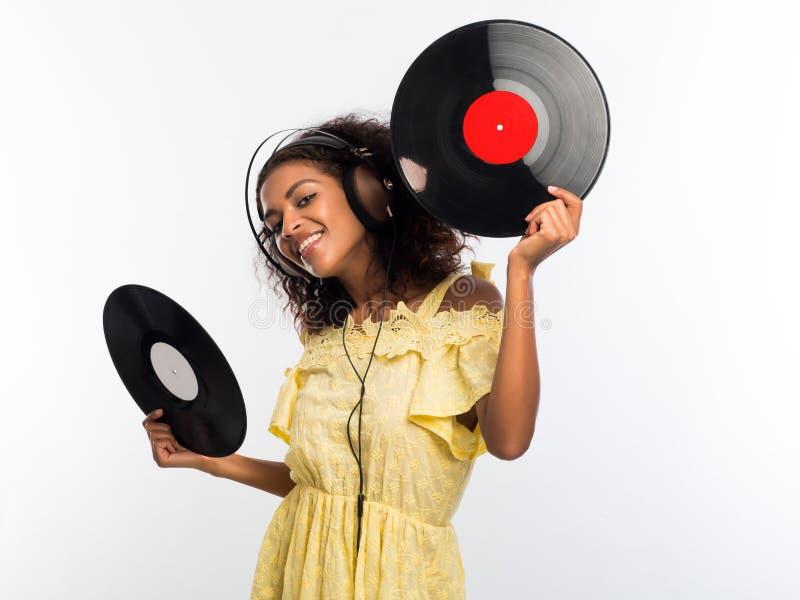 Νέα όμορφη γυναίκα αφροαμερικάνων με τα ακουστικά στο κίτρινο φόρεμα που απολαμβάνει και που χορεύει με τα βινυλίου αρχεία στο λε στοκ εικόνα
