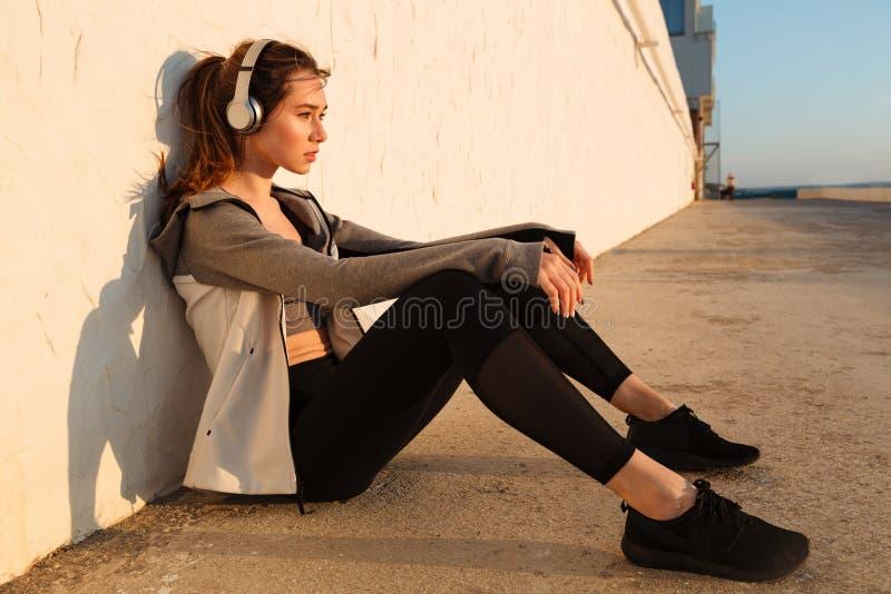 Νέα όμορφη γυναίκα δρομέων που στηρίζεται μετά από το τρέξιμο, που ακούει τη μουσική στοκ εικόνες