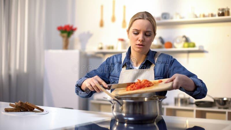 Νέα όμορφη γυναίκα δυστυχισμένη με το μαγείρεμα στην κουζίνα, που τρυπιέται και που κουράζεται των μικροδουλειών στοκ εικόνες