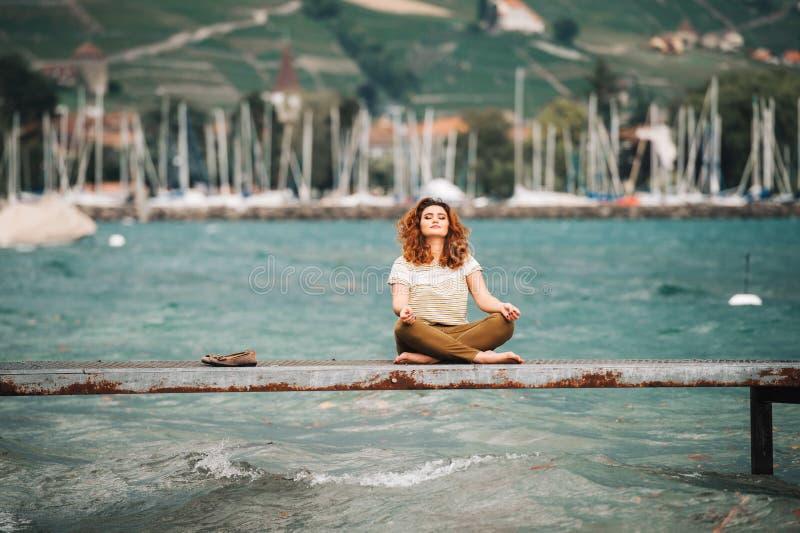 Νέα όμορφη γυναίκα θέσης λωτού στη λίμνη στοκ φωτογραφία με δικαίωμα ελεύθερης χρήσης