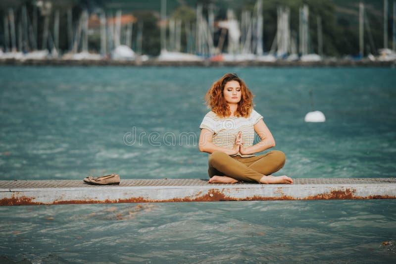 Νέα όμορφη γυναίκα θέσης λωτού στη λίμνη στοκ εικόνες