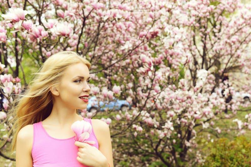 Νέα όμορφη γυναίκα κοντά στο δέντρο magnolia με τα λουλούδια στοκ φωτογραφία
