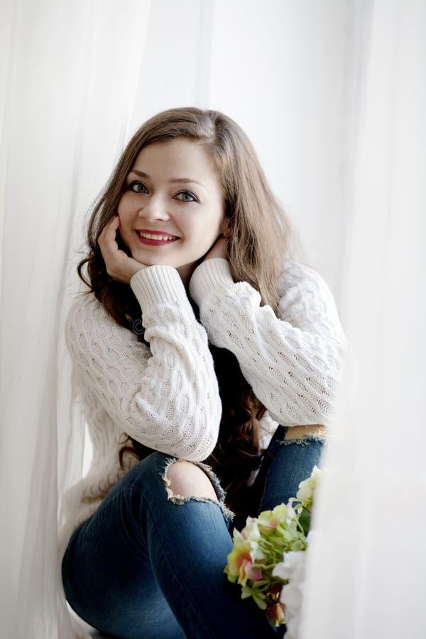 Νέα όμορφη γυναίκα με μακρυμάλλη στο πουλόβερ και το τζιν παντελόνι που κάθεται κοντά στο παράθυρο στοκ φωτογραφία με δικαίωμα ελεύθερης χρήσης