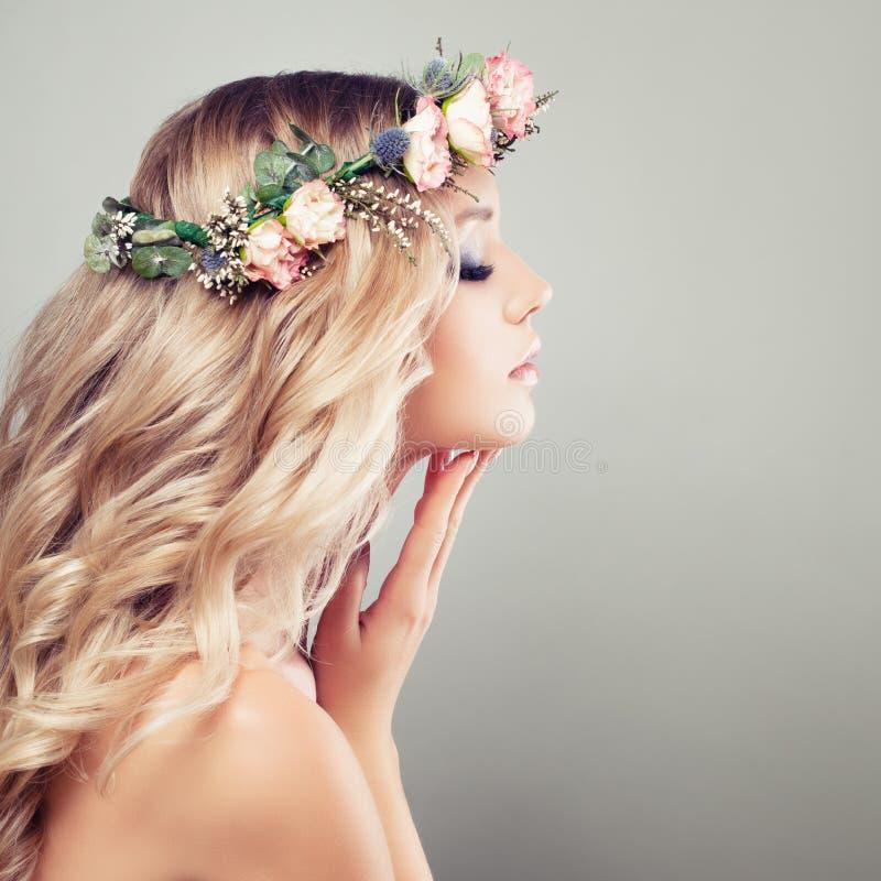 Νέα όμορφη γυναίκα με τα λουλούδια στην τρίχα της στοκ φωτογραφίες με δικαίωμα ελεύθερης χρήσης