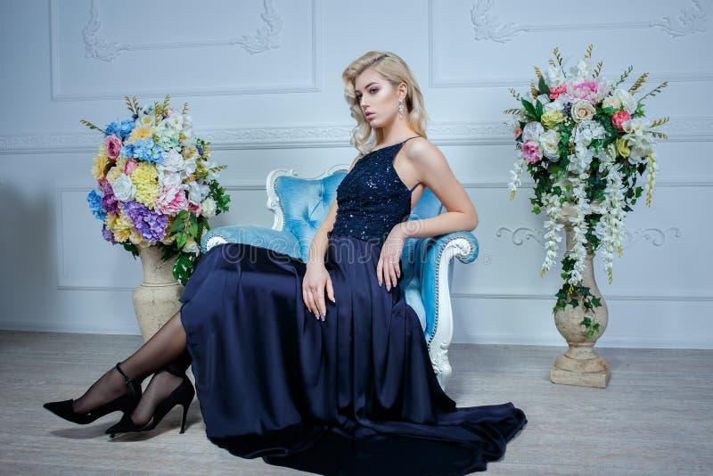Νέα όμορφη γυναίκα με τα μακριά ξανθά μαλλιά στην κομψή σκούρο μπλε τοποθέτηση φορεμάτων στο άσπρο στούντιο στοκ φωτογραφία