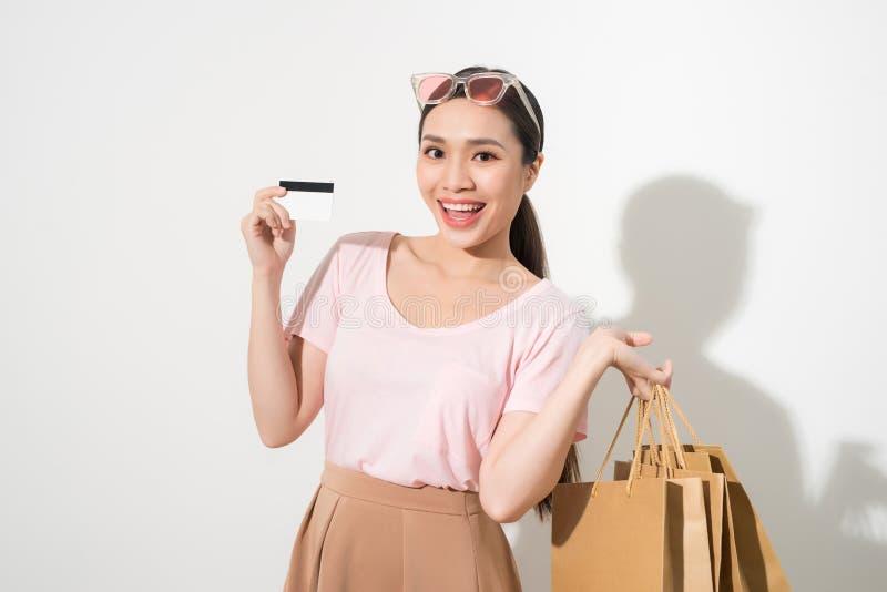 Νέα όμορφη γυναίκα με την πιστωτική κάρτα υπό εξέταση και τσάντες αγορών εκμετάλλευσης πέρα από το άσπρο υπόβαθρο στοκ εικόνες
