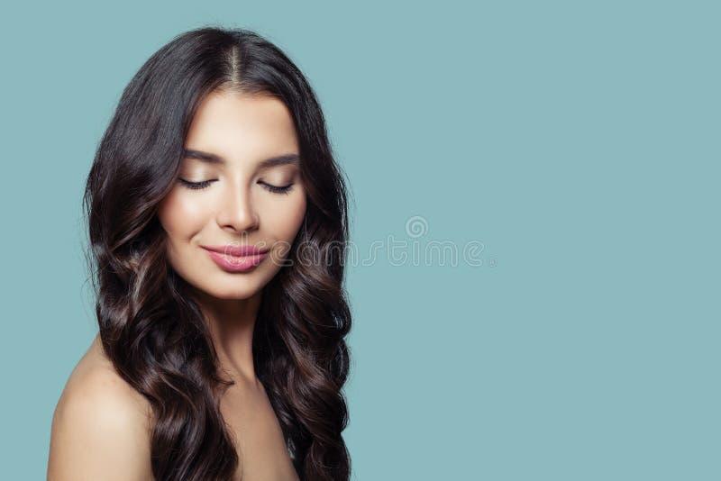 Νέα όμορφη γυναίκα με τη μακριά υγιή τρίχα και φυσικό makeup στο μπλε υπόβαθρο στοκ εικόνα με δικαίωμα ελεύθερης χρήσης
