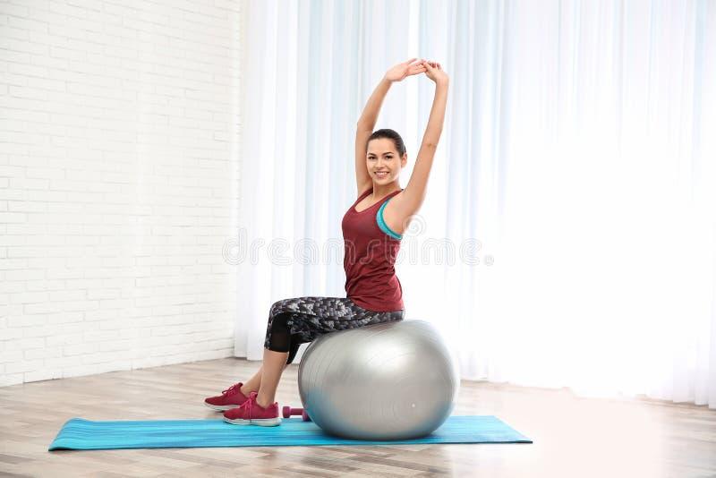 Νέα όμορφη γυναίκα με τη σφαίρα που κάνει την άσκηση Workout και ικανότητα στοκ εικόνα