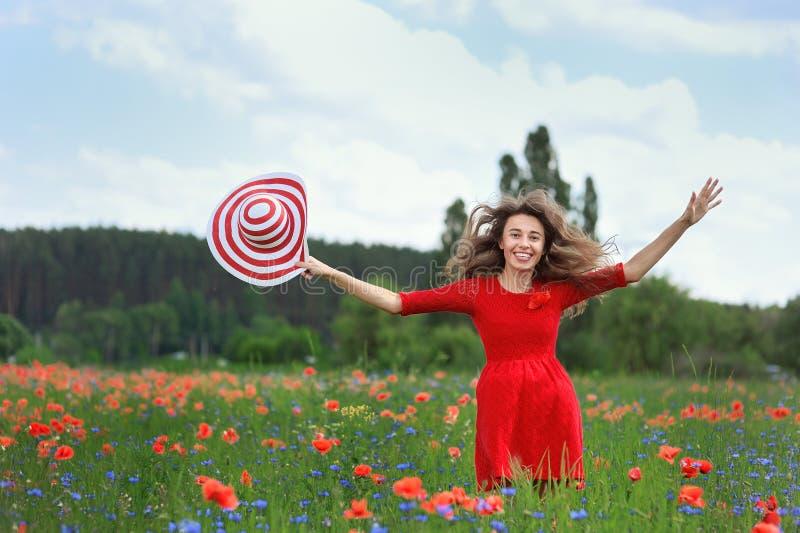 Νέα όμορφη γυναίκα με τον αυξημένο τομέα παπαρουνών όπλων την άνοιξη Ελευθερία έννοιας και καλοκαίρι ευτυχίας στοκ φωτογραφίες με δικαίωμα ελεύθερης χρήσης