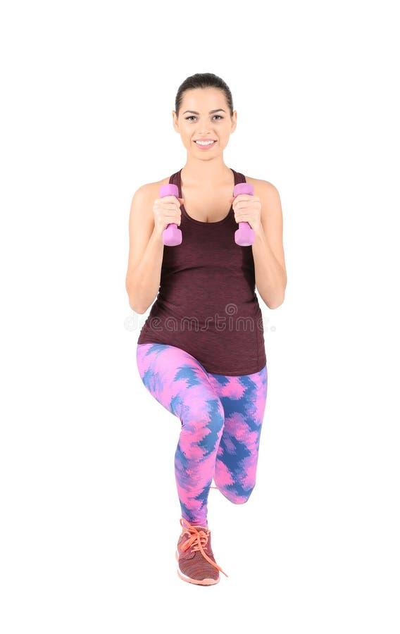 Νέα όμορφη γυναίκα με τους αλτήρες που κάνουν την άσκηση στο άσπρο υπόβαθρο στοκ εικόνες