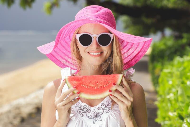 Νέα όμορφη γυναίκα με το καρπούζι που φορά το ρόδινα ψαθάκι και το SU στοκ εικόνα