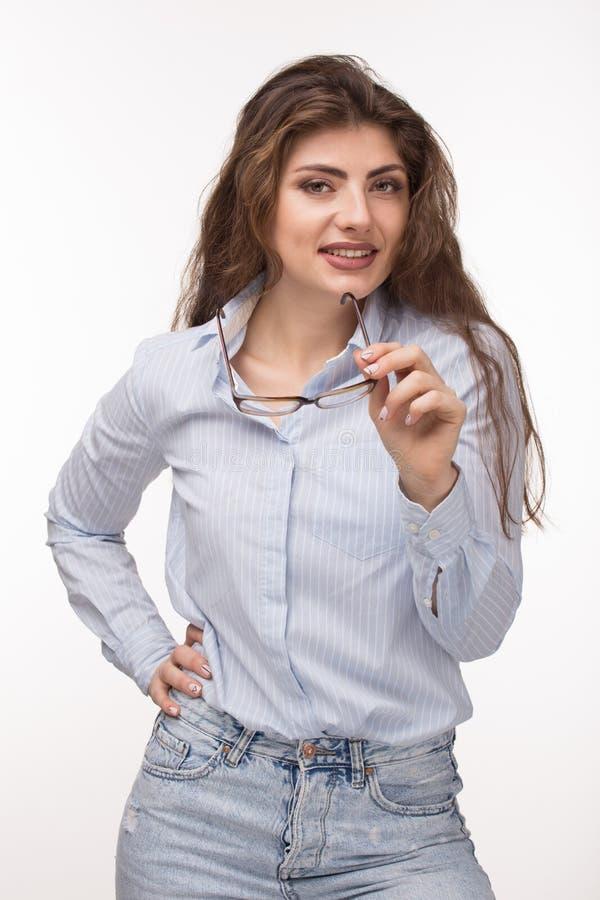 Νέα όμορφη γυναίκα με το μακροχρόνιο σγουρό χαμόγελο τρίχας, που κρατά τα γυαλιά διαθέσιμα Σκέψη για την επιλογή στοκ εικόνες