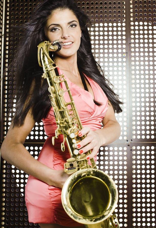 Νέα όμορφη γυναίκα με το παιχνίδι saxophone στο κόμμα στοκ εικόνα