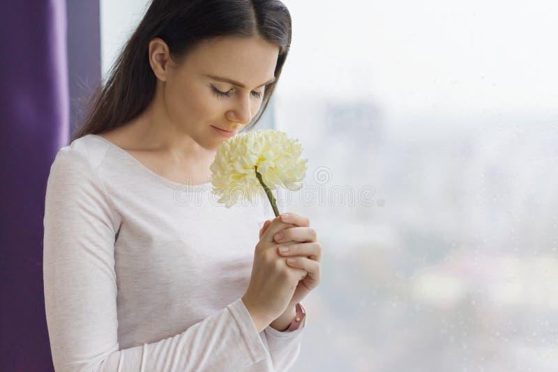 Νέα όμορφη γυναίκα με το φυσικό makeup, πολύ και υγιής καφετιά τρίχα, κορίτσι με μεγάλο χλωμό - κίτρινο λουλούδι κοντά στο παράθυ στοκ φωτογραφίες